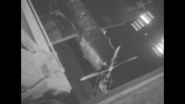 Two shots of electronic graph tracking results of wind tunnel test / overhead view through open roof of wind tunnel of military airplane in tunnel /...