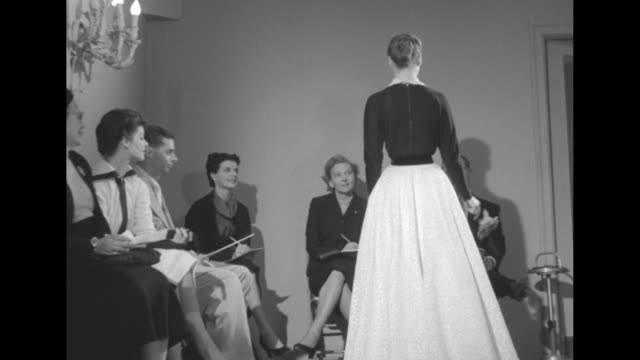 two shots of fashion model displaying long lightcolored skirt with dark bodice she is wearing to people sitting on chairs around sides of room collar... - collar stock videos & royalty-free footage