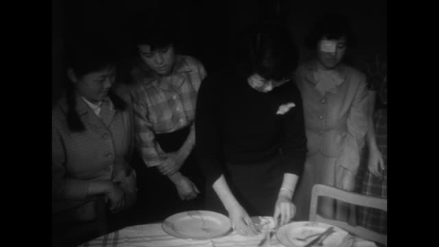 two shots of female instructor standing at table showing japanese women standing around table how to set table / japanese woman setting table while... - eating utensil stock videos & royalty-free footage