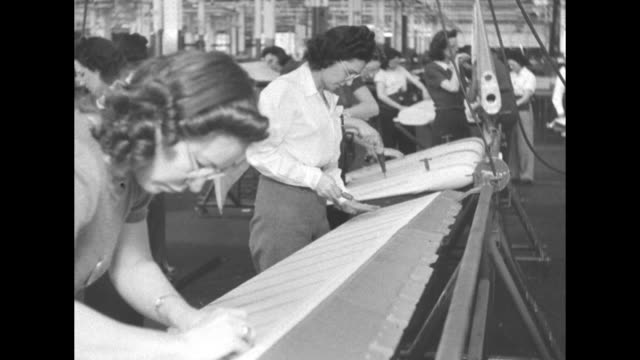 Two shots of female workers painting ailerons / two shots of female workers screwing bolts into ailerons / female workers painting ailerons and...