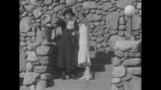 vídeos de stock e filmes b-roll de two shots of first lady grace coolidge on right and louise wood, wife of retired us general leonard wood standing together talking on a rock-walled... - política e governo