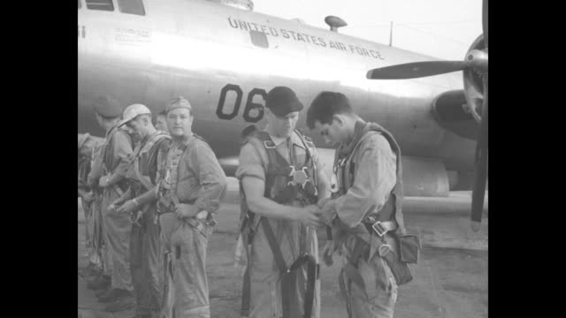 Two shots of flight crew standing on tarmac next to bomber putting on flight gear / pan across bombers parked on airfield to ground crew working on...