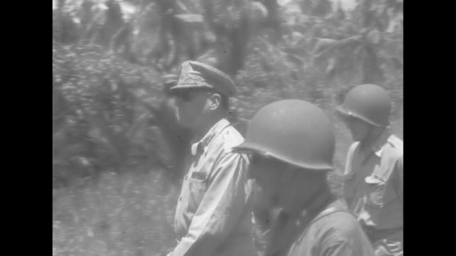 Two shots of Gen Douglas MacArthur accompanied by officers walking through jungle / MacArthur standing with officers / CU MacArthur / Note exact day...