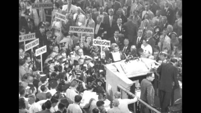 Two shots of Gen Douglas MacArthur and group of men walking through delegates towards rostrum at the International Amphitheatre in Chicago he is to...