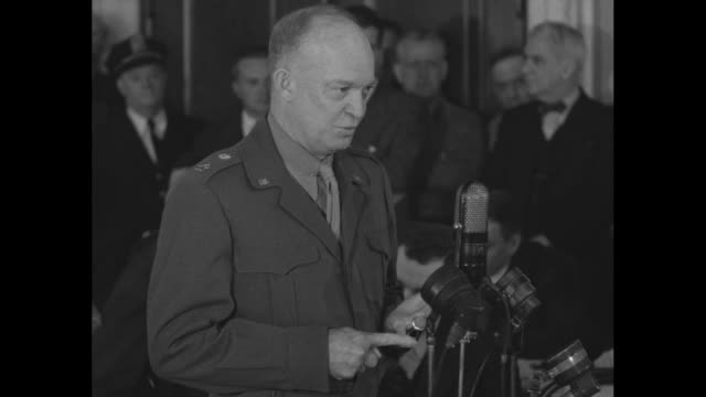 vídeos de stock, filmes e b-roll de two shots of gen. dwight eisenhower, army chief of staff, standing at microphones testifying, reporters and audience behind him; he argues in favor... - equipamento de mídia