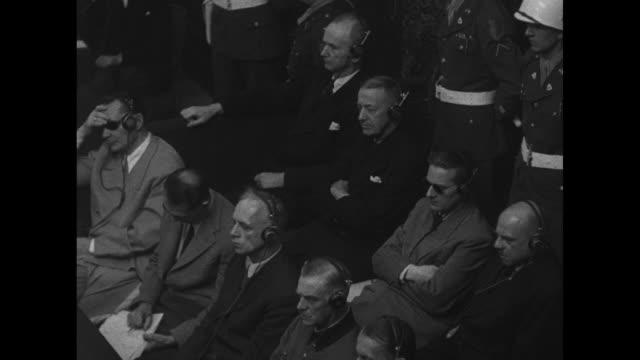 two shots of german lawyers for nazi defendants sitting at table listening to judge norman birkett reading verdict / nazi defendants karl doenitz... - nuremberg trials stock videos & royalty-free footage