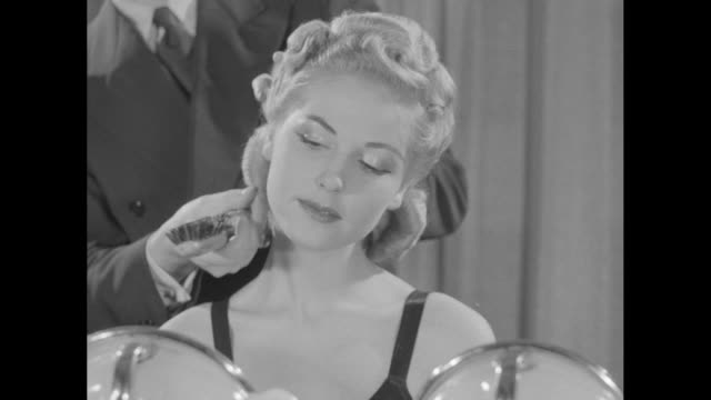 stockvideo's en b-roll-footage met two shots of hairdresser andre de lembre demonstrating hairdressing technique on seated woman / three women in bathing suits seated at makeup tables... - haarborstel