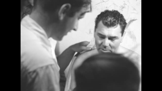 two shots of jack dempsey talking to reporter holding microphone / dempsey talking to reporter, dempsey's manager steps up next to him and talks to... - pesi massimi video stock e b–roll