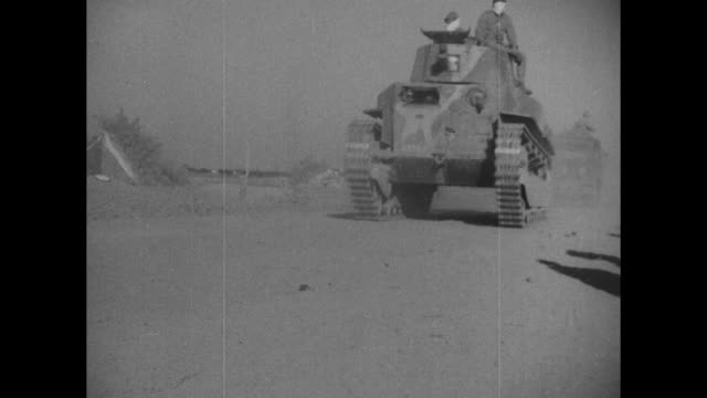 Two shots of Japanese tanks rolling along past camera during Battle of Shanghai in Second SinoJapanese War / soldiers kneel and squat put down rifles...