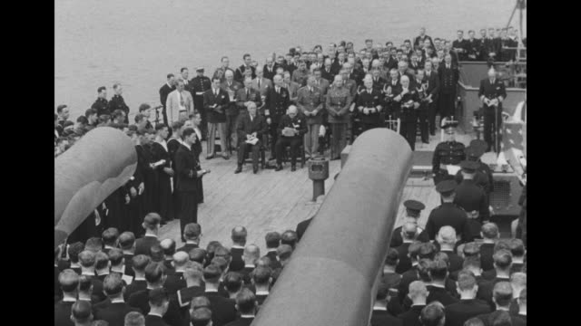 Two shots of large group of US and British military personnel attending religious service on deck of ship US President Franklin Roosevelt and British...