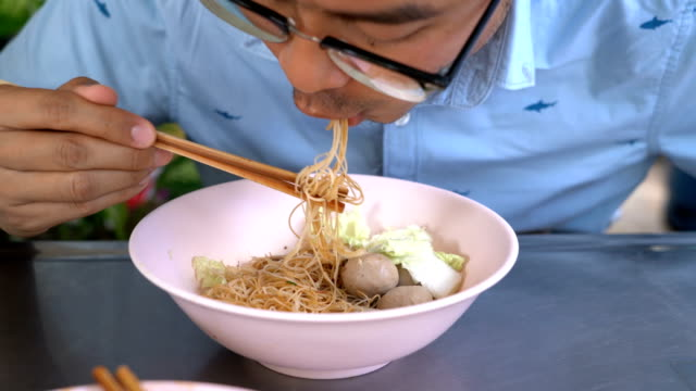 two shots of man eating rice vermicelli noodle with pork ball - rice ball stock videos & royalty-free footage