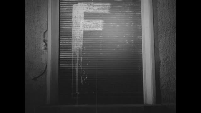 two shots of man holding paint bucket while another man paints large letter f on wall / two shots of letter f painted on wall / man holds paint... - reportage bild bildbanksvideor och videomaterial från bakom kulisserna