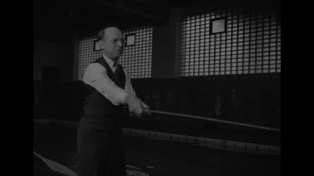 two shots of man paddling plastic canoe in pool indoors while other man stands in prow casting plastic fly rod / man and woman in lab coats spread... - centro di ricerca video stock e b–roll