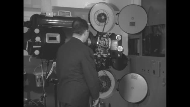 two shots of man standing next to running film projector in room / two shots of same man loading reel onto projector / close view of man's hand... - film projector stock videos & royalty-free footage