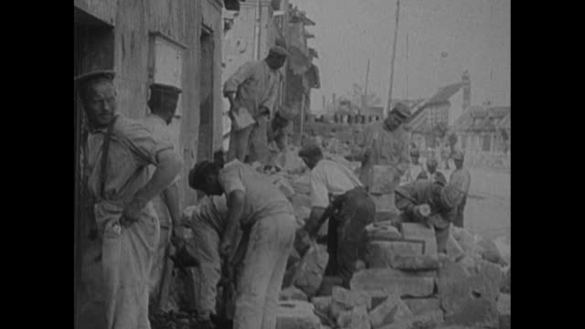 vidéos et rushes de two shots of men clearing debris / men preparing cement blocks to use in repairing building / men building wood structures / men sawing planks with... - belgique