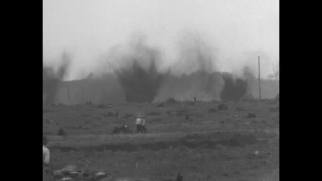 two shots of men gathered in marsh area where other men are digging ditch / two shots of series of explosions going off in same area / note: exact... - marsh stock videos & royalty-free footage