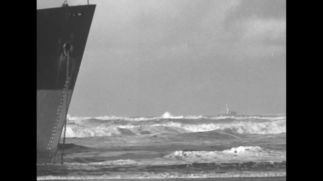 Two shots of men hauling cable from ship across beach ship in background / man winding winch on beach / prow of ship and surf rushing past it / US...