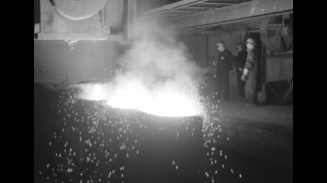 two shots of molten steel pouring into molds / four shots of men standing on platform watching molten steel pouring into row of molds / us steel... - ペンシルベニア州点の映像素材/bロール