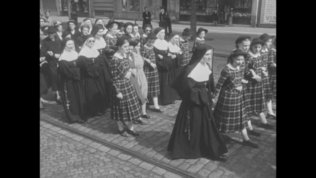 two shots of nuns and schoolgirls in uniforms walking in procession behind hearse carrying coffin of louis braille inventor of raised printing - assistive technology stock videos & royalty-free footage