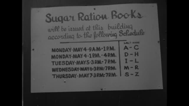two shots of people standing in long line on sidewalk / sign on building reading sugar ration books and giving schedule for registration / two shots... - sugar stock videos & royalty-free footage