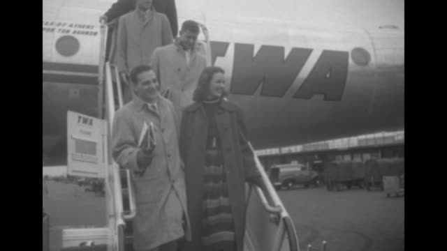 Two shots of plane carrying 'Look' magazine allAmerican football players taxiing at airport / woman and players coming down steps from plane / two...