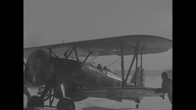 two shots of plane on cleared area / plane taxiing towards camera, man holds wing guiding plane forward / pilot in cockpit, bundled up against the... - war stock-videos und b-roll-filmmaterial