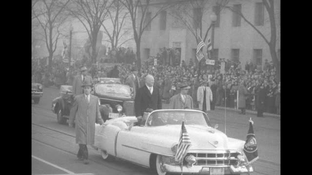 two shots of pres dwight eisenhower standing up in back seat of open car waving at crowd as it drives down street first lady mamie eisenhower sitting... - back to front stock videos & royalty-free footage