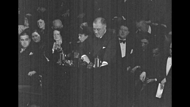Two shots of Pres Franklin Roosevelt standing and speaking at podium on stage in Worcester MA auditorium with officials sitting behind him including...