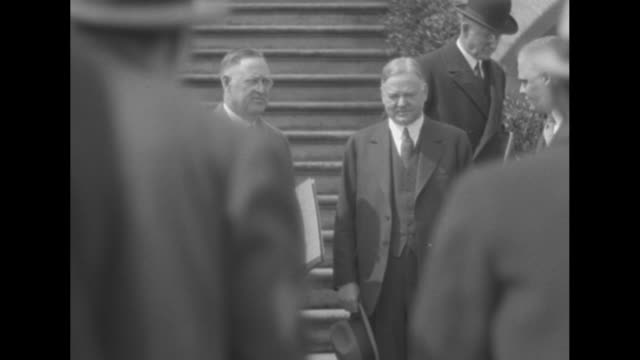 two shots of pres herbert hoover standing on right in front of steps of building answering question of census bureau enumerator / director of us... - census stock videos & royalty-free footage