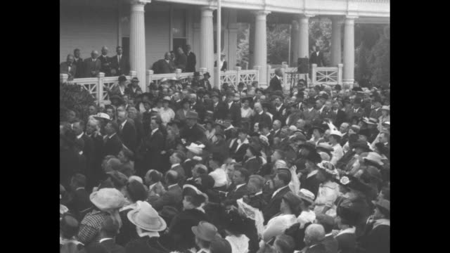 Two shots of Pres Woodrow Wilson standing on porch of his home speaking to crowd / two shots of Wilson shaking hands of people walking past him in...
