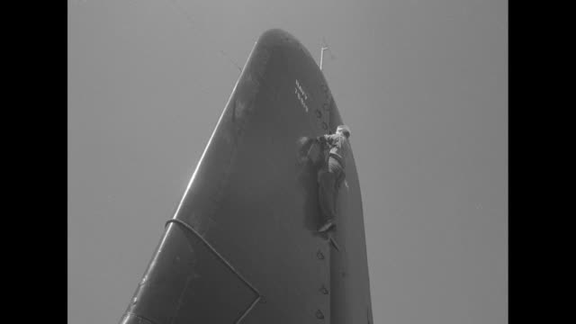 two shots of sailor climbing up tail rudder of airplane / sailor sitting on top of tail rudder / two shots of sailors standing in line on horizontal... - stabilisers stock videos & royalty-free footage