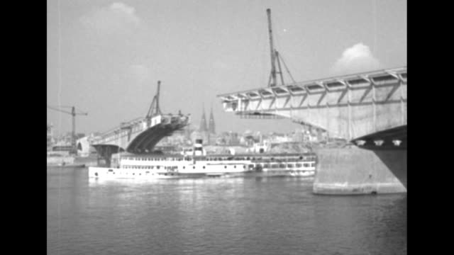 two shots of ship passing under uncompleted bridge on rhine river / two shots of boats going down river in front of parliament building under... - ノルトラインヴェストファーレン州点の映像素材/bロール