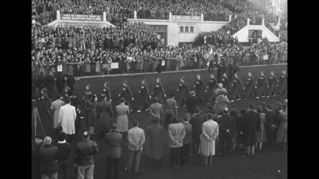 two shots of single file line of russian runners in sweat suits marching onto running course crowd on either side / shot of crowd in stands and on... - collegetröja bildbanksvideor och videomaterial från bakom kulisserna