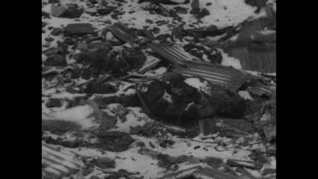 two shots of snow-covered street / dead bodies lying on ground inside ruined factory in shenyang / allied correspondents looking at body / two shots... - manchuria stock videos & royalty-free footage