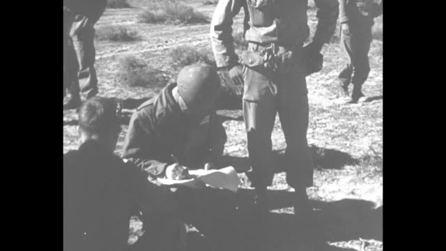 vídeos de stock e filmes b-roll de two shots of soldier sitting down writing down information from radiation badges handed to him by other soldiers soldiers sitting and standing around... - arma de destruição em massa