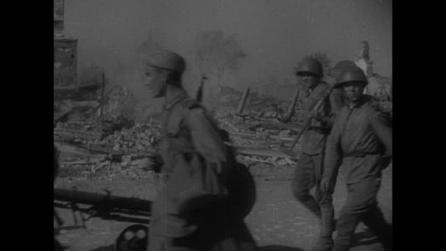 two shots of soviet soldiers marching along street wrecked buildings and rubble in background / children running towards camera to greet soldiers /... - 1944 stock-videos und b-roll-filmmaterial