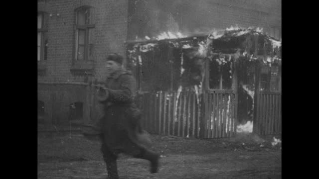 vídeos de stock e filmes b-roll de two shots of soviet soldiers running past burning buildings / horses hauling artillery piece past burning building as soldiers run along with it /... - world war ii