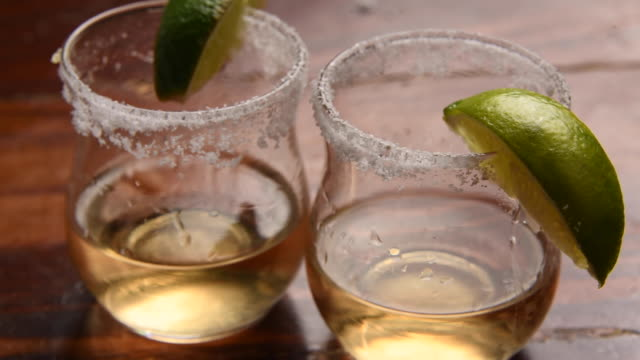 two shots of tequila over a wooden table - lime stock videos & royalty-free footage
