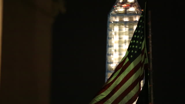 vidéos et rushes de two shots of the washington memorial and an american flag in washington dc - obelisk