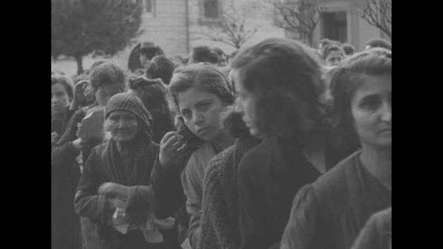 two shots of trucks and red cross vehicle driving down street / italian women standing in line in street / close view of children standing in street,... - world war ii video stock e b–roll