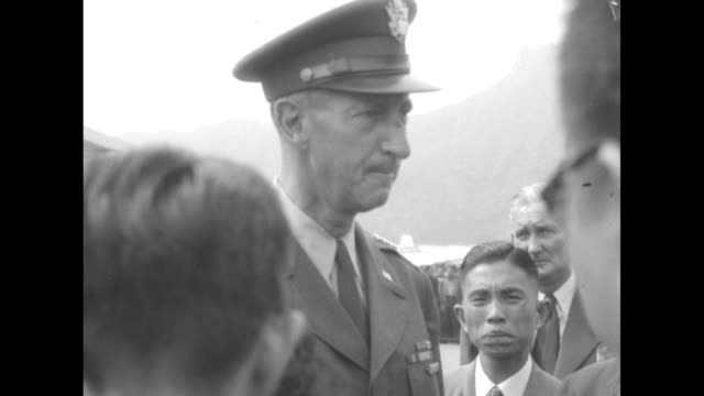 vidéos et rushes de two shots of us general mark clark standing for photo opportunity at hong kong airport with british officers and us officer / cu clark talking to... - adlai stevenson
