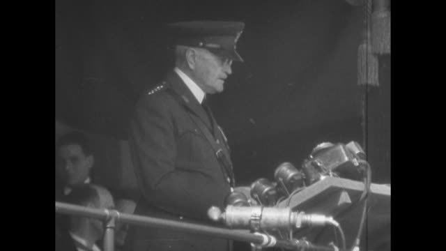 Two shots of US officers sitting on platform / SOT Gen John Pershing standing at microphones on platform giving speech honoring US soldiers who...