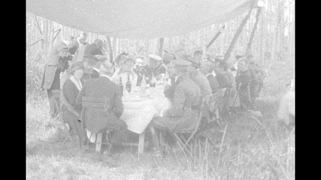 Two shots of US Pres Woodrow Wilson and Belgium's King Albert sitting next to one another at head of table talking to Wilson's wife Edith / standing...