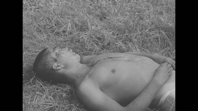 two shots of us soldiers marching down road / close shot of filipino guerillas / dead japanese soldier lying on ground / note: exact day not known - 日本の軍事力点の映像素材/bロール