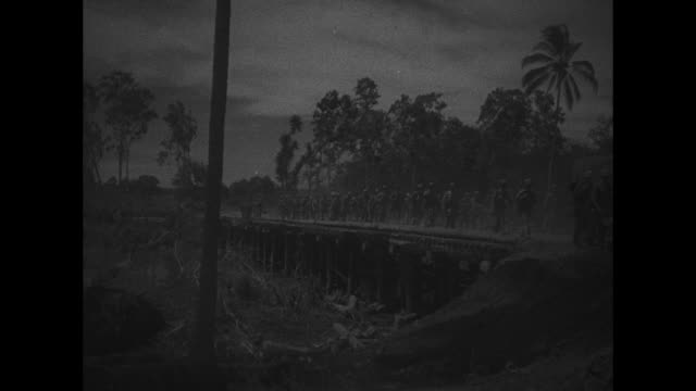 two shots of us soldiers walking through jungle / two shots of soldiers walking down both sides of road / soldiers walking across bridge / soldiers... - world war ii点の映像素材/bロール