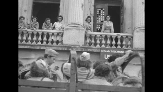 two shots of wacs leaving building and getting onto truck / wacs watching from balcony of building / truck pulls away wacs on balcony and wacs on... - womens army corps stock videos & royalty-free footage