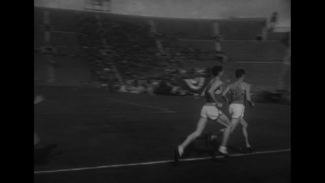 two shots of wes santee warming up before race in los angeles memorial coliseum / santee in sweat clothes / start of 1/2mile run / runners racing... - plakette stock-videos und b-roll-filmmaterial