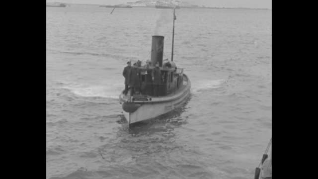 two shots of william murdoch riding on boat in boston harbor / murdoch gets off boat, walks along dock, climbs up ladder to pier where group of... - kommunismus stock-videos und b-roll-filmmaterial