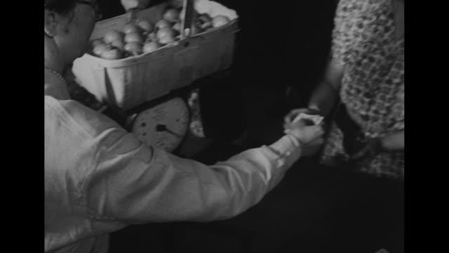 two shots of women carrying baskets of fruit into market / two shots of women weighing fruit baskets / woman purchasing fruit basket/ vs people... - 缶詰にする点の映像素材/bロール