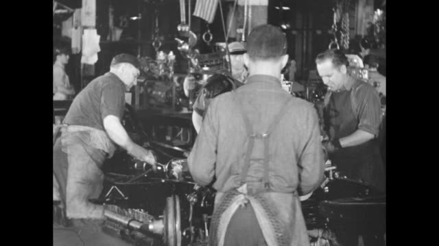 vídeos de stock e filmes b-roll de two shots of workers assembling military automobiles / two shots of workers working on automobile engines as they come down assembly line / two shots... - general motors